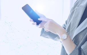 白い明るい背景と日本人女性のIOTイメージとテクノロジーのホログラムのCGグラフィックスの写真素材 [FYI04954024]