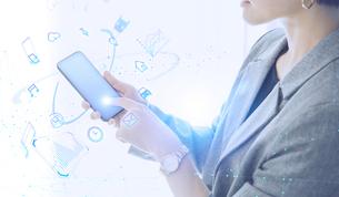 白い明るい背景と日本人女性のIOTイメージとテクノロジーのホログラムのCGグラフィックスの写真素材 [FYI04954026]