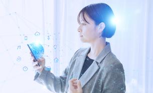 白い明るいオフィスで日本人女性がスマートフォンでIOTを操作するテクノロジーとホログラムのCGグラフィックスの写真素材 [FYI04954028]