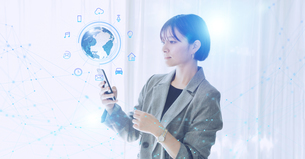 白い明るいオフィスで日本人女性がスマートフォンでIOTを操作するテクノロジーとホログラムのCGグラフィックスの写真素材 [FYI04954029]