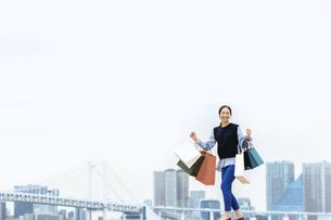 買い物袋を沢山持ってジャンプする女性(セール・爆買い)の写真素材 [FYI04954808]