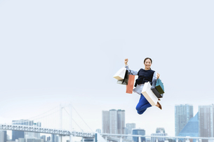 買い物袋を沢山持ってジャンプする女性(セール・爆買い)の写真素材 [FYI04954809]