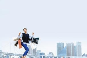 買い物袋を沢山持つ女性(セール・爆買い)の写真素材 [FYI04954813]