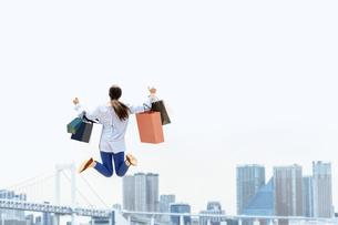 買い物袋を沢山持ってジャンプする女性(セール・爆買い)の写真素材 [FYI04954818]