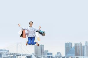 買い物袋を沢山持ってジャンプする女性(セール・爆買い)の写真素材 [FYI04954819]