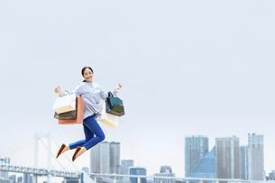 買い物袋を沢山持ってジャンプする女性(セール・爆買い)の写真素材 [FYI04954821]