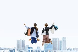 買い物袋を沢山持ってジャンプする女性2人(セール・爆買い)の写真素材 [FYI04954825]