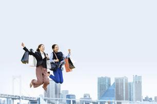 買い物袋を沢山持ってジャンプする女性2人(セール・爆買い)の写真素材 [FYI04954826]