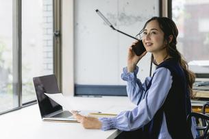 電話をする働く女性(自宅・テレワーク・オフィス)の写真素材 [FYI04954849]