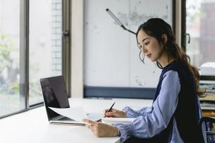 資料を手にして働く女性(自宅・テレワーク・オフィス)の写真素材 [FYI04954850]