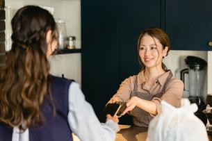 カフェでスマホ決済をする女性(飲食店・テイクアウト)の写真素材 [FYI04954901]
