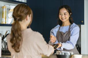 カフェでスマホ決済をする女性(飲食店・テイクアウト)の写真素材 [FYI04954907]