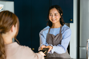 カフェでスマホ決済をする女性(飲食店・テイクアウト)の写真素材 [FYI04957574]