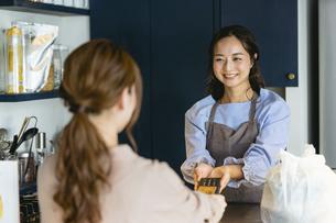 カフェでタッチ決済をする女性(カード決済・非接触型・非接触型カード)の写真素材 [FYI04957611]