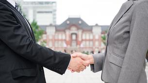 屋外で握手をする男女(顔なし)の写真素材 [FYI04957697]