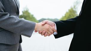 屋外で握手をする男女(顔なし)の写真素材 [FYI04957701]
