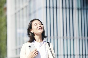 スマホを持ちオフィス街を歩く若い女性の写真素材 [FYI04958541]