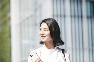 スマホを持ちオフィス街を歩く若い女性の写真素材 [FYI04958543]