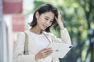 タブレット端末を持ちオフィス街を歩く若い女性の写真素材 [FYI04958550]