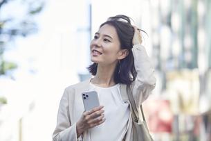スマホを持ちオフィス街を歩く若い女性の写真素材 [FYI04958554]