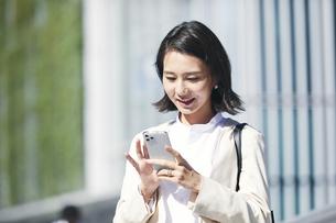 スマホを持ちオフィス街を歩く若い女性の写真素材 [FYI04958556]