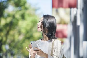 スマホを持ちオフィス街を歩く若い女性の写真素材 [FYI04958563]