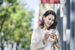 スマホを持ちオフィス街を歩く若い女性の写真素材 [FYI04958569]