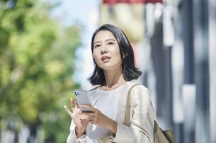 スマホを持ちオフィス街を歩く若い女性の写真素材 [FYI04958572]