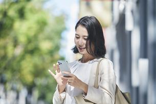 スマホを持ちオフィス街を歩く若い女性の写真素材 [FYI04958575]