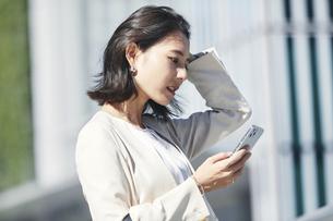 スマホを持ちオフィス街を歩く若い女性の写真素材 [FYI04958578]