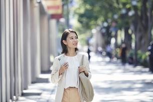 スマホを持ちオフィス街を歩く若い女性の写真素材 [FYI04958582]