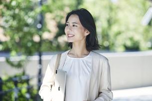 タブレット端末を持ちオフィス街を歩く若い女性の写真素材 [FYI04958598]