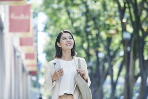 スマホを持ちオフィス街を歩く若い女性の写真素材 [FYI04958601]