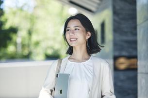 タブレット端末を持ちオフィス街を歩く若い女性の写真素材 [FYI04958603]