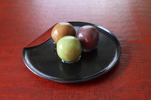 漆塗りの板背景のお皿にのせた餡子玉の写真素材 [FYI04958675]