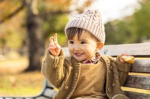 公園のベンチに座る赤ちゃんの写真素材 [FYI04959387]