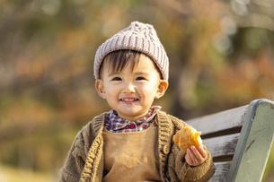 公園のベンチに座る赤ちゃんの写真素材 [FYI04959394]