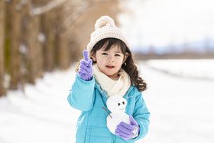 人差し指を立てる雪だるまを持った女の子の写真素材 [FYI04959396]