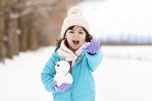 叫んでいる雪だるまを持った女の子の写真素材 [FYI04959404]
