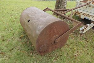 公園の芝生の上に置かれた錆びたガーデニングローラーの写真素材 [FYI04959532]